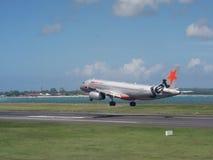 在巴厘岛机场的Jetstar空中航线平面着陆 免版税库存照片