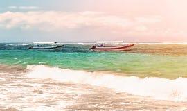 在巴厘岛靠岸有与两条小船的海视图有海浪线的在与云彩的一个晴天在天际水平的视图 库存图片