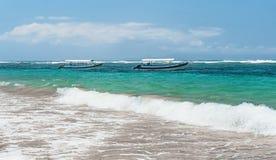 在巴厘岛靠岸有与两条小船的海视图有海浪线的在与云彩的一个晴天在水平的天际 免版税图库摄影