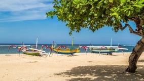 在巴厘岛,准备好三条的小船靠岸航行 库存图片