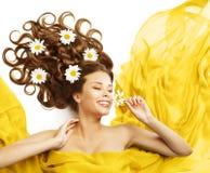 在头发,秀丽式样嗅到的花卷曲发型的妇女花 免版税库存图片