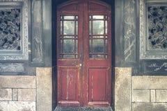 在黑古色古香的墙壁上的红色土气门 免版税库存照片