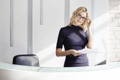 在总台后的美丽的白肤金发的友好的妇女,管理员谈话由电话 阳光在现代办公室 库存照片