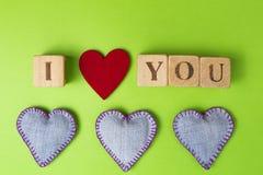 在绿叶背景清楚地说明我爱你牛仔裤和土气字母表块的华伦泰心脏 顶视图 复制 库存照片