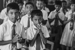 在他们吃食物前,学校孩子祈祷 免版税库存照片