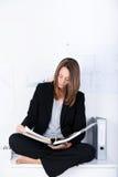 在黏合剂的女实业家读书 免版税库存图片