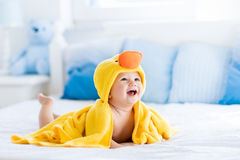 在浴以后的逗人喜爱的婴孩在黄色鸭子毛巾 免版税库存照片