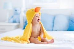 在浴以后的逗人喜爱的婴孩在黄色鸭子毛巾 免版税库存图片