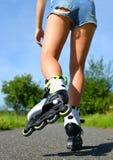 在轴向冰鞋的女性腿 免版税库存照片