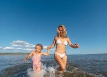 在水和女儿跑的母亲 库存照片