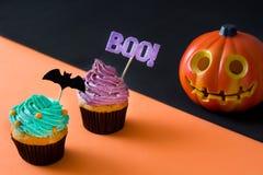 在黑和橙色背景的两块万圣夜杯形蛋糕 免版税库存照片