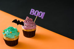 在黑和橙色背景的两块万圣夜杯形蛋糕 免版税库存图片