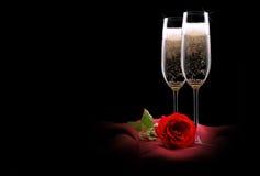 在黑和红色丝绸的香宾玻璃与花 库存照片