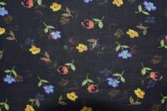 在黑织品样式背景的花 免版税库存图片
