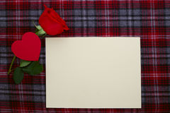 在织品的红色玫瑰与白纸 免版税库存照片