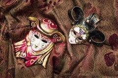 在织品背景的两个化妆舞会狂欢节面具 免版税库存照片