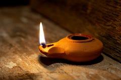 在黏土做的古老中东石油灯在木桌 免版税库存照片