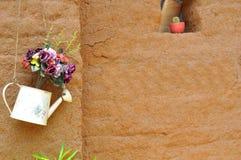 在黏土墙壁上的花 库存图片