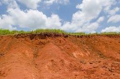 在黏土小山和蓝天顶部的绿草 库存图片