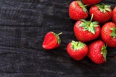 在黑土气木背景的红色新鲜的草莓 库存图片