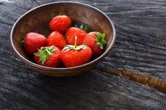 在黑土气木背景的红色新鲜的草莓 免版税库存照片