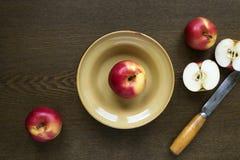 在黏土盘的苹果在木板 免版税图库摄影