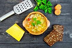 在黏土碗的汤蔬菜通心粉汤在黑委员会上面 免版税库存照片