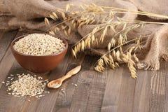 在黏土碗的燕麦粥,燕麦茎在木头背景的  库存图片