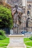 在巴黎圣母院旁边的教宗若望保禄二世雕象在巴黎,法国 免版税库存照片