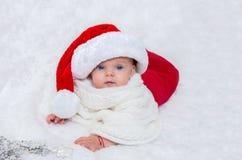 在戴圣诞节的床上的女婴一个圣诞老人帽子 库存照片