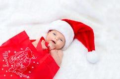 在戴圣诞节的床上的逗人喜爱的女婴一个圣诞老人帽子 免版税库存图片
