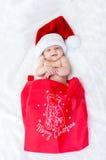 在戴圣诞节的床上的逗人喜爱的女婴一个圣诞老人帽子 库存图片