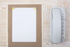 在织地不很细纸和电话的白色板料 免版税库存图片