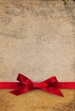 在织地不很细纸背景的红色丝带弓 免版税库存图片