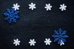 在黑织地不很细背景的白色和蓝色圣诞节雪花装饰 免版税库存照片