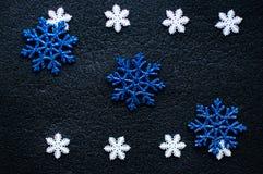 在黑织地不很细背景的白色和蓝色圣诞节雪花装饰 免版税库存图片