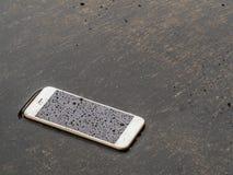 在洪水地板上投下的湿巧妙的电话 免版税库存照片