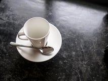 在黑地板上的空的白色杯子 库存图片