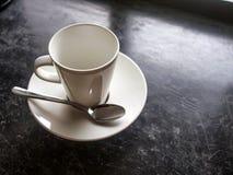 在黑地板上的空的白色杯子 库存照片