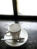 在黑地板上的空的白色杯子 免版税图库摄影