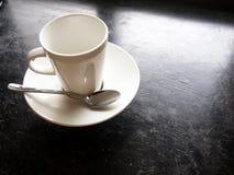 在黑地板上的空的白色杯子 免版税库存图片