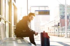 在驻地的愉快的年轻人等待的火车与袋子 免版税库存照片