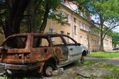 在围场的被烧下来的车residental房子 免版税库存照片