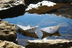在水坑的两艘纸船 库存图片