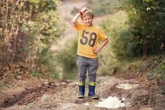 在水坑附近的棘手的面孔男孩在乡下公路 库存照片