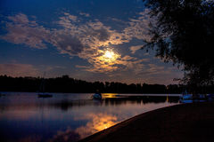 在水坝和湖的日落有剪影渔船的 库存照片