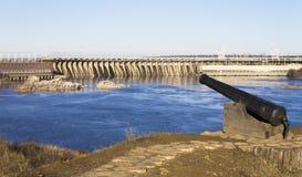 在水坝和水电站的背景的古老枪 图库摄影