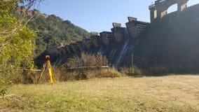 在水坝墙壁的一个美好的日出视图的三脚架 库存图片