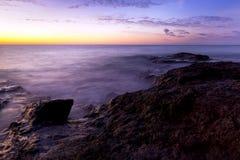 在费埃特文图拉岛岩石岸的日出  图库摄影
