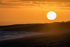 在巴塔哥尼亚海滩的红色日出 免版税库存照片